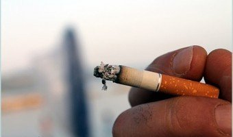 holding a burning cigarette